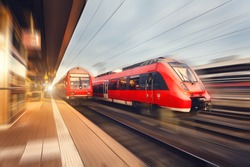 Modern high speed red passenger trains at sunset. Railway station in Nuremberg, Germany. Railroad with motion blur effect. Industrial concept landscape