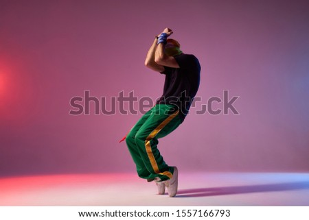 Modern hip hop dancer frozen in movie, standing on tiptoe, covering head with hands, expressing dance element, practicing in dance studio, full of energy break dancer Stockfoto ©
