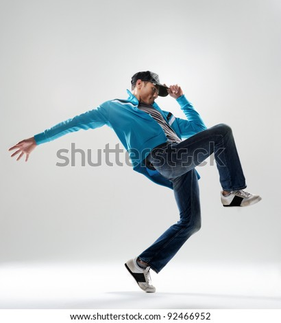 modern hip hop dancer lifts his leg and does some moves while dressed in trendy modern clothing