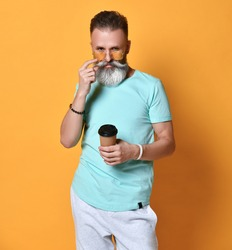 Modern hipster man holding a disposable paper cup, standing on a bright orange background. A middle-aged man drinks morning coffee or tea. Takeaway coffee concept.