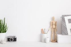 Modern home decor mock up with camera, dummy, houseplant. Artist workspace.