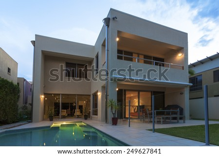 Modern home exterior with pool at dusk