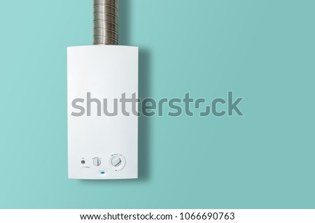 Modern home gas boiler, water heater. An isolated gas stove on a pastel turquoise background. Water heating, ecology. Concept lifestyle.