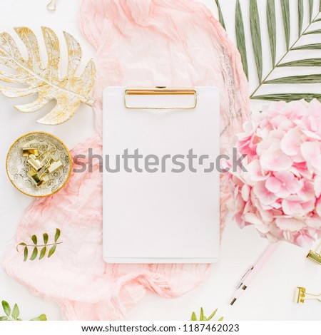 Modern home office desk workspace with blank paper clipboard, pink hydrangea flower bouquet, tropical palm leaf, pastel blanket, monstera leaf plate on white background. Flatlay, top view.