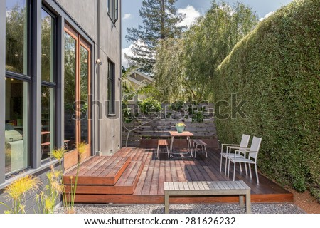 Modern home with large windows and amazing outside terrace with table and chairs. Green house with deck and zen garden.