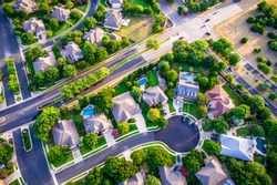 Modern homes and houses in suburb. High aerial view above thousands of homes north of Austin , Texas in Round Rock Suburbia sunset colors of new development neighborhood straight down angle cul de sac