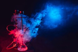 Modern hookah, shisha on a smoky black background with neon lighting and smoke. Place for your text