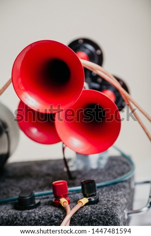 Modern horn. Pneumatic horn with three red tubes stands on a close-up stand #1447481594