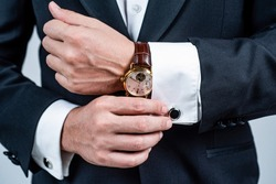 Modern horology. Wrist watch worn with formal suit. Portable timepiece. Time management. Horology concept. Professional punctuality. Business etiquette