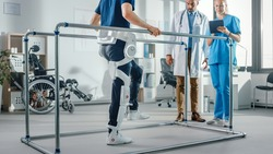 Modern Hospital Physical Therapy: Patient with Injury Walks Wearing Advanced Robotic Exoskeleton. Physiotherapy Rehabilitation Scientists, Engineers use Tablet Computer to Help Disabled Person