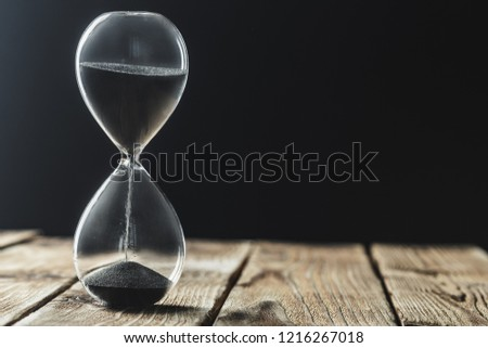 Modern hourglass on wooden background