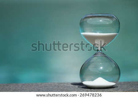 Modern Hourglass -- sand trickling through the bulbs of a crystal sand glass. every second counts. symbol of time. summer countdown.