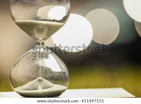 Modern Hourglass -- sand trickling through the bulbs of a crystal sand glass on bokeh background. every second counts. symbol of time. countdown. sandglass.