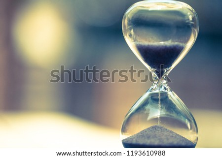 Modern Hourglass with blurry window-view background -- sand trickling through the bulbs of a crystal sand glass. every second counts. symbol of time. countdown.
