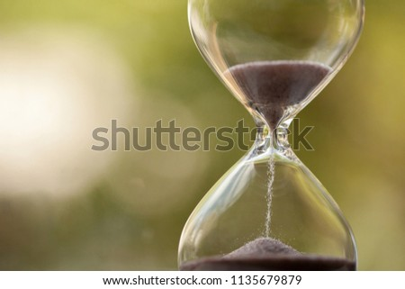Modern Hourglass with green background -- sand trickling through the bulbs of a crystal sand glass. every second counts. symbol of time. countdown. #1135679879