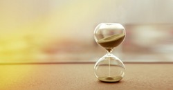 Modern hourglass with sand color background, as time passing concept for business deadline, urgency and running out of time