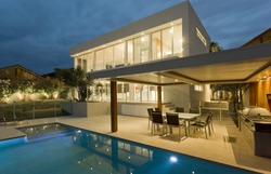 Modern house at dusk with swimming pool and barbecue in backyard