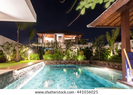Modern house including a swimming pool in the middle illuminated with lights starting from the garden  at night