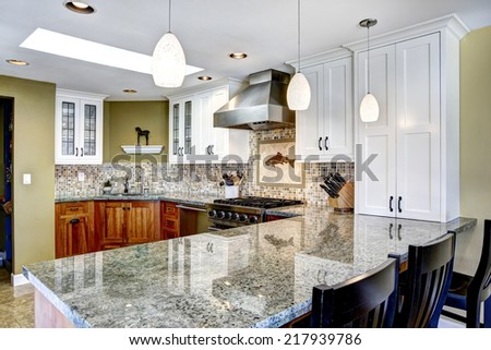 Photo of Modern house interior. White and brown kitchen room with shiny granite tops and mosaic back splash trim