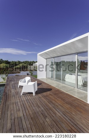 Modern house with garden swimming pool and wooden deck