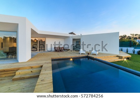 Modern house with garden swimming pool and wooden deck #572784256