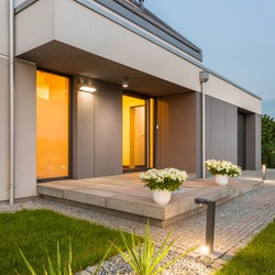 Modern house with nice lawn and surrounded by decorative outdoor lights