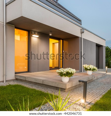 Modern house with nice lawn and surrounded by decorative outdoor lights #442046731