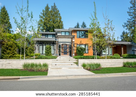 Modern house with wood trim exterior and beautiful landscaping. Home exterior design.