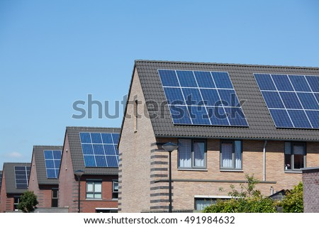 Modern houses with solar panels on the roof for alternative energy. #491984632