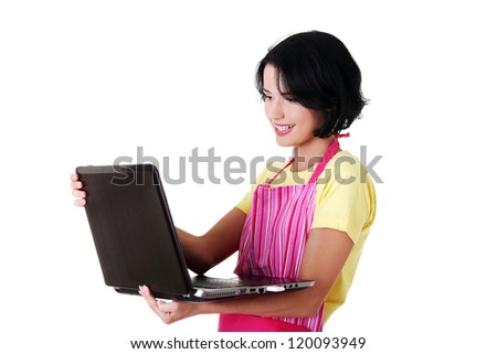 Modern housewife or female worker with laptop wearing pink apron