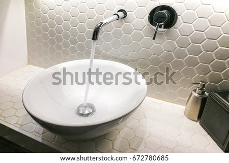 Modern hygienic wash basin with running clean water from tap faucet - Shutterstock ID 672780685
