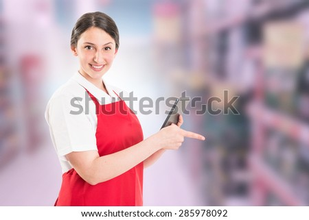 Modern hypermarket female worker using tablet to check supply