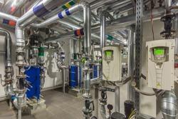 Modern independent heating system in boiler room. Pipelines, water pump, valves, manometers