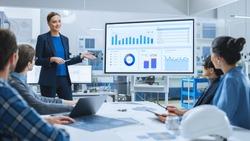 Modern Industrial Factory Meeting: Confident Female Engineer Uses Interactive Whiteboard, Makes Report to a Group of Engineers, Managers Talks and Shows Statistics, Growth and Analysis Information