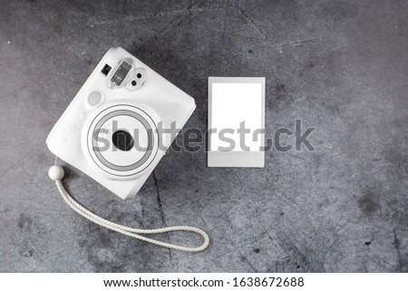 Modern instant camera, metal background. Top view, tender minimal flat lay style composition.