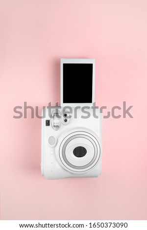 Modern instant camera, photo pink wooden background. vertical photo. retro camera. 1980s