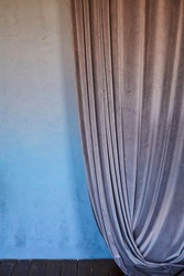 Modern interior blue wall with drapery, grey velvet curtain on the wall. Blurred background, frame