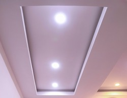 Modern interior design for living room, conference room and hotels. False ceiling co-ply design using gypsum or plaster of paris. Illuminated new home interior with false ceiling lighs.