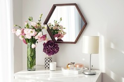 Modern interior details. Light room with mirrow, flowers, night lamp and other objects