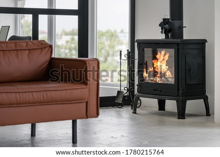 Modern interior house with bright living room, fire in new fireplace, comfortable leather couch on concrete floor against glass wall on background