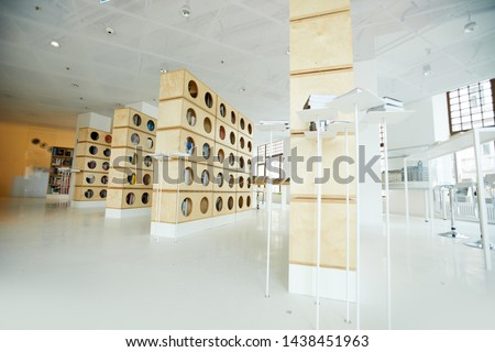 Modern interior of bookstore with wooden bookcases and high tables for leisure of customers, copy space #1438451963