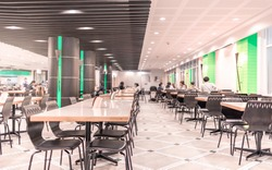 Modern interior of cafeteria or canteen with chairs and tables, eating room in selective focus