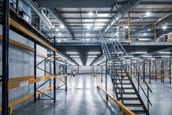Modern interior of empty  industrial warehouse. New distribution storehouse. Metal construction. Staircase to second floor.