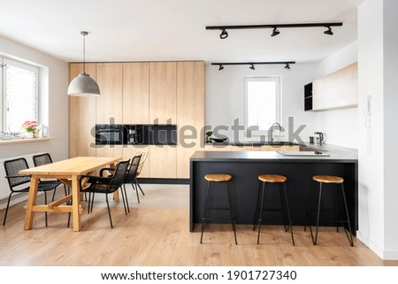 Modern interior of kitchen with kitchen island, granite kitchen island, wooden furnitureand stylish table and chairs. Spacious and luxurious space in apartment.
