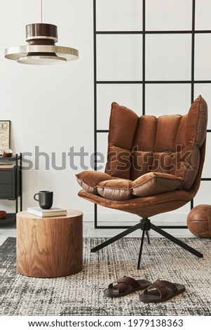 Modern interior of living room with design brown armchair, side table, pendatn lamp, loft wall, slippers, carpet, decoration and elegant personal accessories in home decor. Template.  Foto stock ©