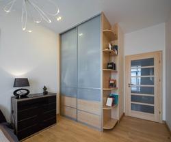 Modern interior of luxury bedroom. Stylish dark dresser. Glass sliding door wardrobe with wooden shelves. Home decor.