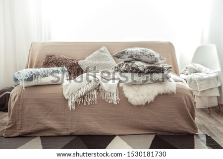 Modern interior of the living room with a sofa and decorative items . Decorative pillows and blankets. Coziness and comfort at home . #1530181730