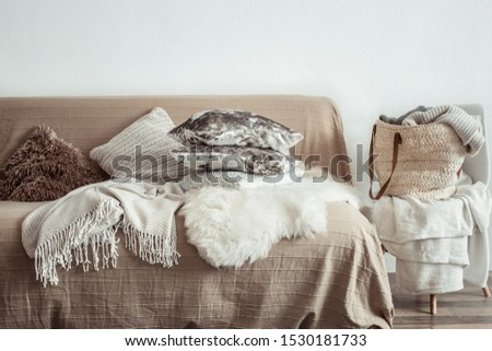 Modern interior of the living room with a sofa and decorative items . Decorative pillows and blankets. Coziness and comfort at home . #1530181733