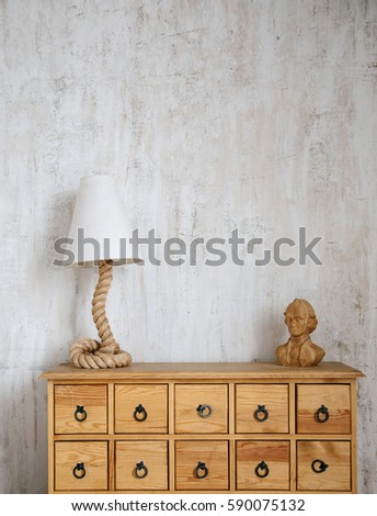 Modern interior photo of cabinet with drawers, rope shaped lamp and wooden abstract man bust model. Concrete wall background.