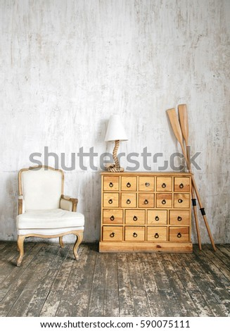 Modern interior photo of cabinet with drawers, rope shaped lamp, cloth armchair and oars. Concrete wall and wooden floor background.